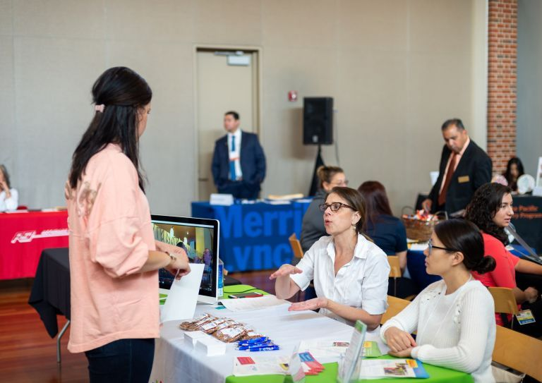 student interacts with employers at career fair