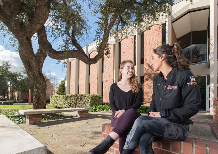 two students sitting on campus