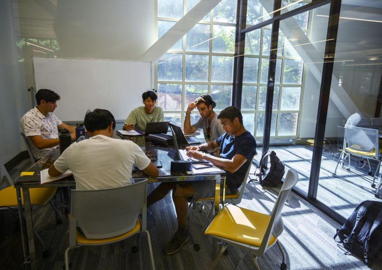 five students studying in a study room