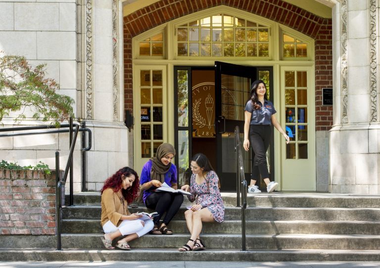 female students sit on the steps of Knoles Hall