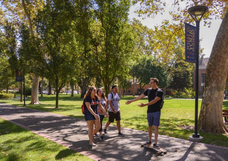 a group of students talking on a path on the stockton campus