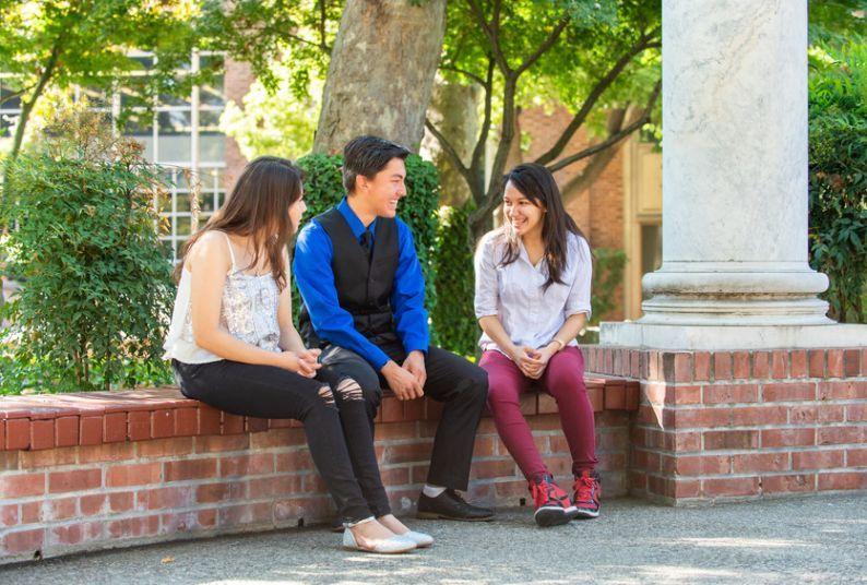 Three University of the Pacific students sit and chat.