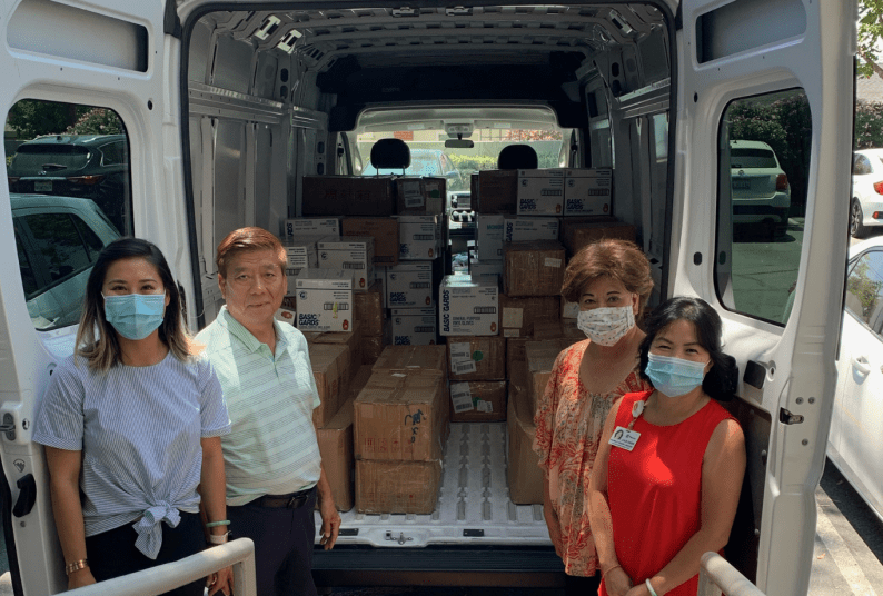 The Chan family next to van full of PPE