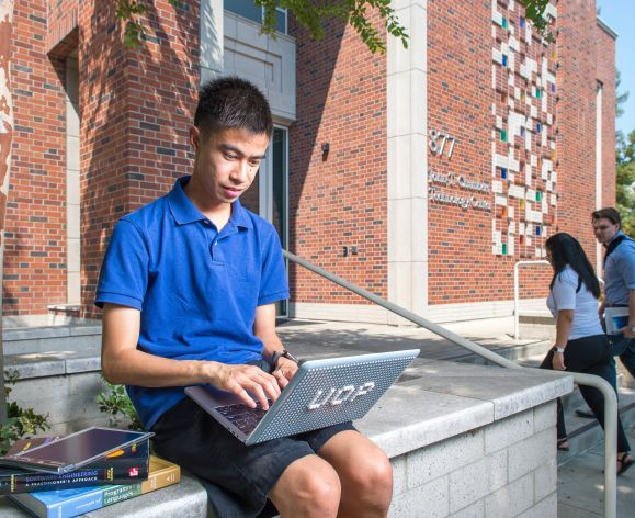 student sitting outside on laptop