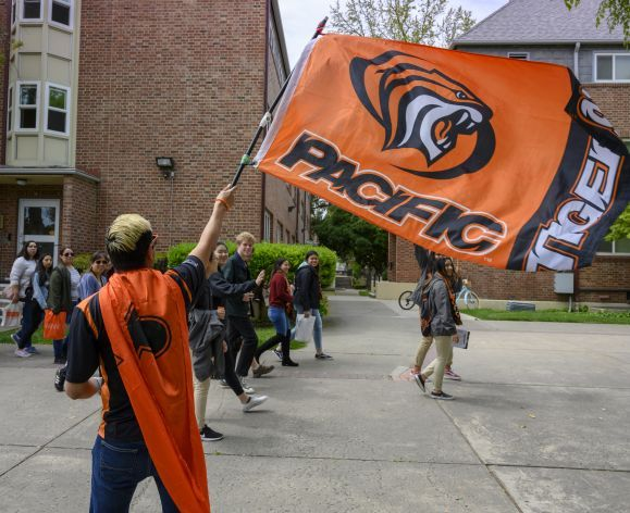 student waving Pacific Tigers flag