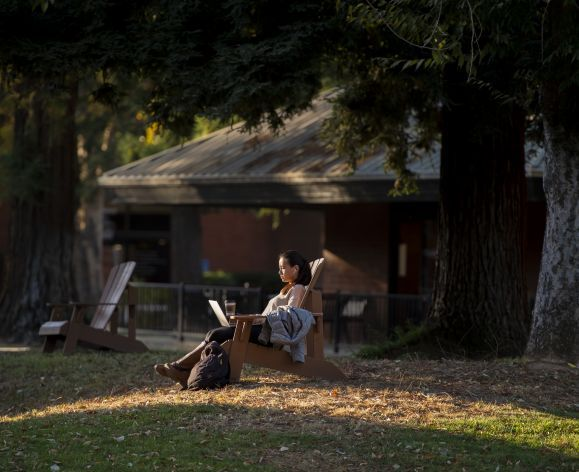 a student reading in the quad on the sacramento campus