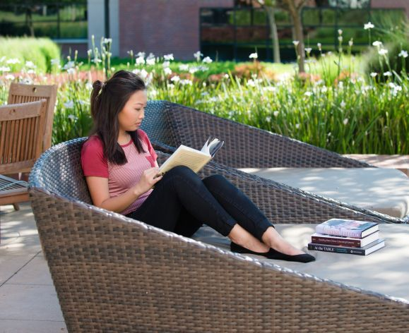 student reading in front of DeRosa Center