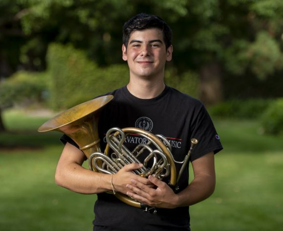 student holding French Horn