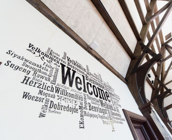 """Welcome"" in multiple languages mural on wall"