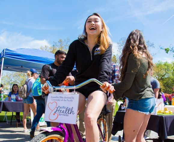 Student riding bike at health fair